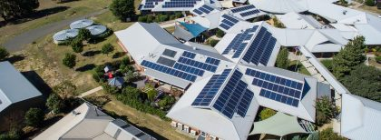 An aerial view of a multi-building health facility with many solar panels on the roof