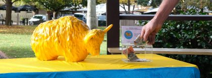 A hand putting a $50 note into a donation box next to a golden yak mascot