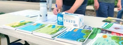 Coloured information cards on a table while a person fills out a form in the background