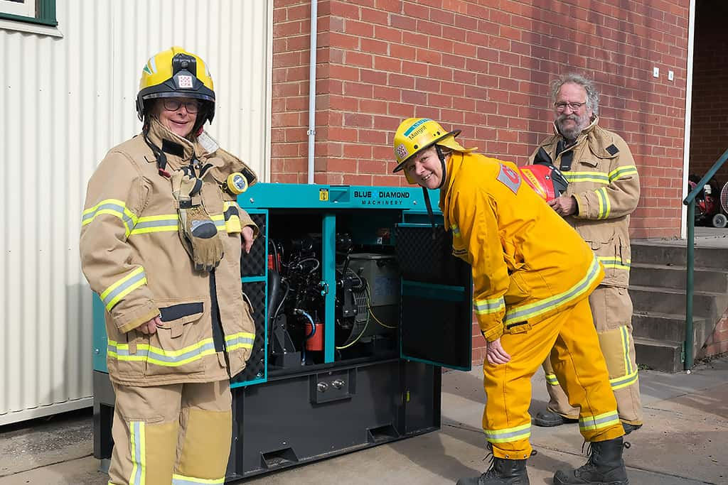 People wearing fire fighting gear checking out a backup generator