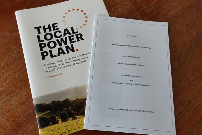 """A photo of a black and white parliamentary bill memorandum and a coloured brochure with the title """"Local Power Plan"""""""